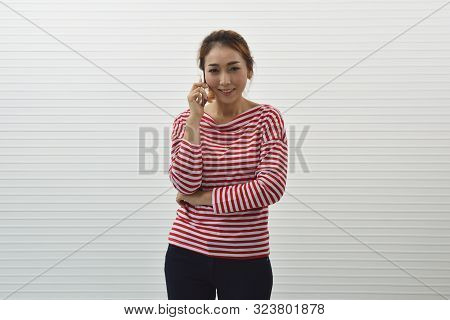 Happy Young Asian Woman Wearing Red And White Stripped Shirt And Jeans Talking On Modern Smart Mobil