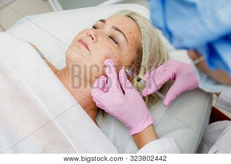 Beautician doing facial injection for woman. Anti-aging revitalization cosmetology procedure poster