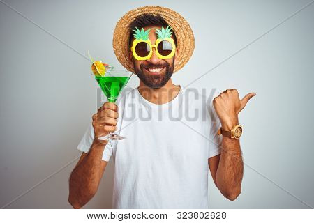 Indian man wearing summer funny look drinking cocktail over isolated white background pointing and showing with thumb up to the side with happy face smiling