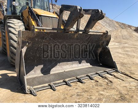Bucket Of Yellow Loader Backhoe Digging A Trench During Road Construction Works. Earthmoving, Excava