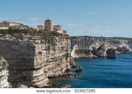 Panoramic View Of The High Vertical Cliffs And The Sea. On The Rock Ancient Tower And Houses