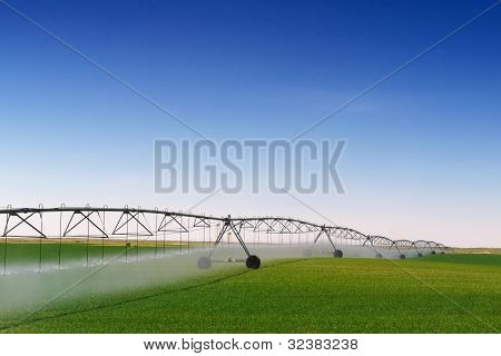 A farm being irrigated with a center pivot sprinkler system poster