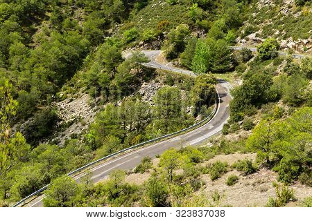 A Section Of Road With Bends Going Through  Mountainous Countryside