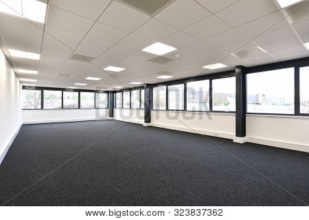 View Of A New Empty Office Area With Windows On Two Sides And Carpeted