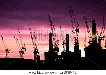 Silhouettes Of Building Cranes At Sunset With Battersea Power Station
