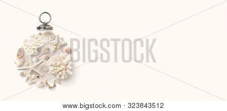 Christmas in July / at the beach / in the southern hemisphere conceptual banner, background or header / hero image with holiday ornament made of shells, starfish and corals, flat lay, copy space