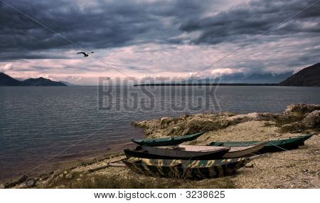 Waterscape With Boats, Flying Bird And Dramatic Sky
