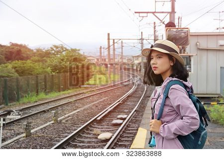 Beautiful Tourist Hold Camera With Hat And Backpack On Train Platform.