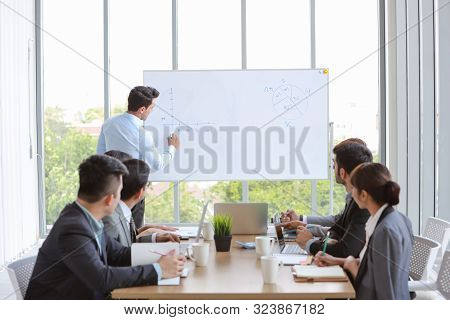 Businessman Coaching In Team Meeting Or Training, Speaker Drawing Graph On White Board (business Sem