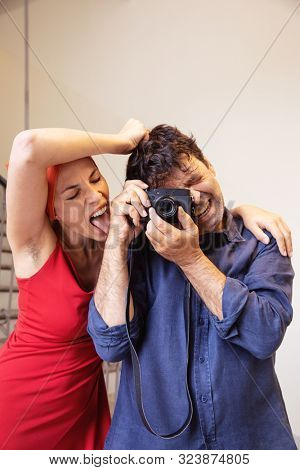 Young attractive woman with hairy armpits licks a hairy arm of a photographer