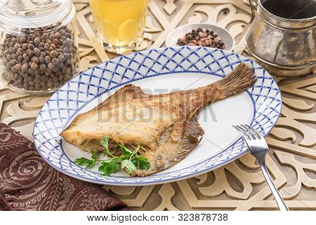 Fried fish flounder with parsley on white plate with glass of lemonade on oriental wooden table side view poster