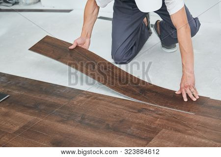 worker joining vinyl floor covering at home renovation