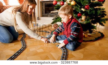 Young Mother Helping Little Son Building Tailways For Toy Train Under Christmas Tree At Living Room.