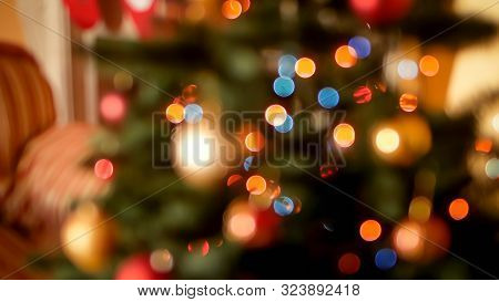 Abstract Blurred Photo Of Glowing Christmas Lights Garlands And Colorful Baubles On Christmas Tree A