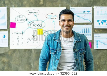 Portrait Of Happy Indian Man In Jeans Jacket Standing In Creative Office Workplace With Document Pla