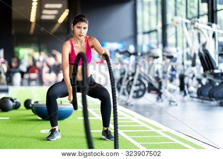 Sporty Asian Woman Exercising With Battle Ropes At The Gym On Green Floor. Strong Female Determine W