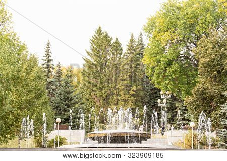 Fontaine In City Park In Autumn Day With Trees