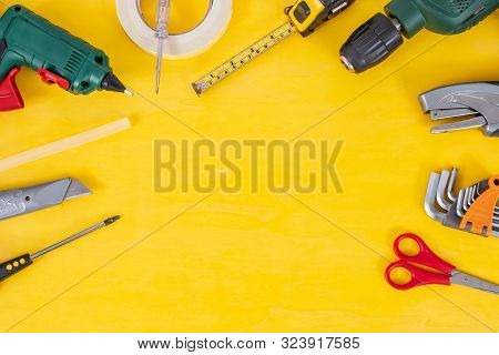 Do It Yourself Tools On Yellow Background. Diy Tools With Copy Space For Text On Yellow Wooden Backg