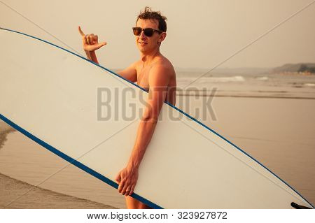 Shaka Hand Gesture Surfers Symbol.young Surfer Man With Surfboard On The Beach Summer Sunset Sea.sur