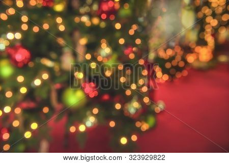 Christmas Tree Blur Background With Bokeh Lights. Xmas Lights On A Pine Tree On A Red Background. Ch