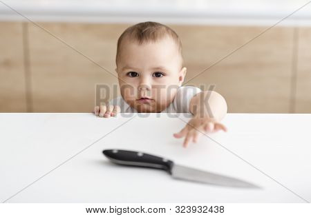Dont Leave Kids Alone. Little Baby Boy Reaching Hand For Sharp Knife On Kitchen Table, Empty Space