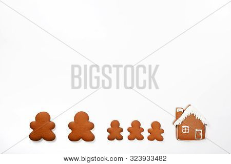 The hand-made eatable gingerbread little man (family) and house on white background poster