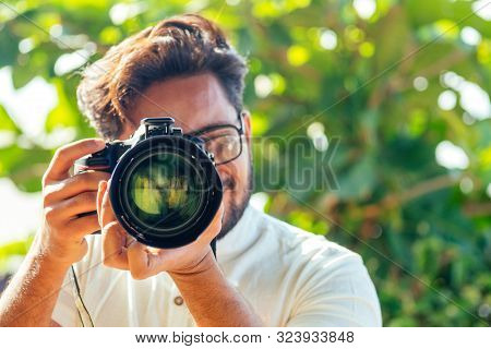Handsome And Confident Indian Man Photographer With A Large Professional Camera Taking Pictures Phot