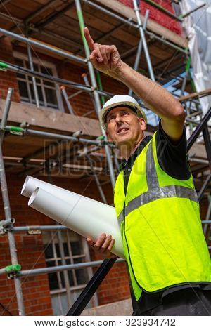 Male builder foreman, worker surveyor, engineer or architect on construction site holding building plans and pointing