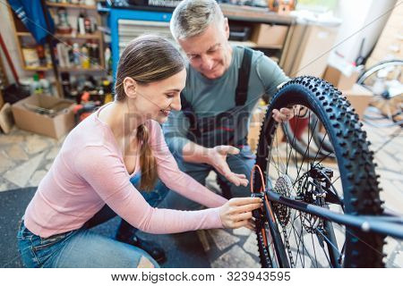 Bike Mechanic and customer looking at the bicycle that needs service and maintenance