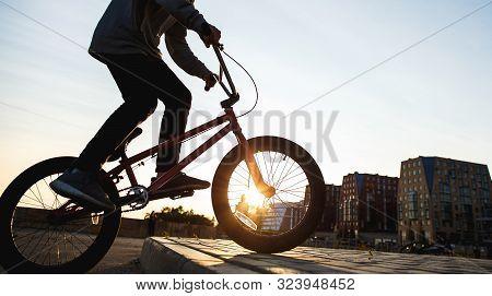 Bmx Rider Rides In The Urban Background Of The Sunset. Evening Training At Bmx. Bmx Concept. Copyspa