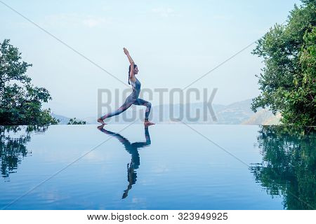 Beautiful Woman Practice Yoga Pose On The Infinity Pool Above The Mountain Peak In The Morning In Fr
