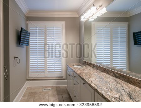 Beautiful bathroom interior with granite countertop and limestone tile floor.