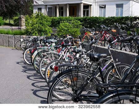 Kumla, Sweden - 11 Jun 2019: Parked Bicycles In Racks On Urban City Street Near A White Building.
