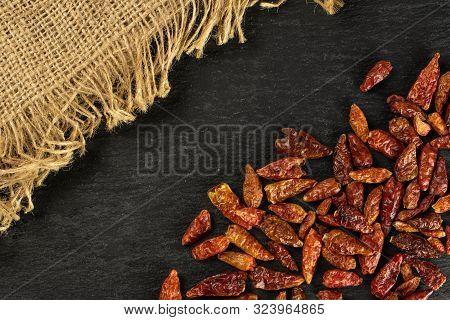 Lot Of Whole Dry Red Chili Pepper Peperoncino On Jute Cloth Flatlay On Grey Stone