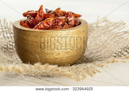 Lot Of Whole Dry Red Chili Pepper Peperoncino In Wooden Bowl On Jute Cloth On White Wood