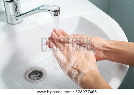 Girl Washes Her Hands With Soap Under Running Water In The Bathroom