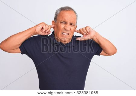Senior grey-haired man wearing black casual polo standing over isolated white background covering ears with fingers with annoyed expression for the noise of loud music. Deaf concept.
