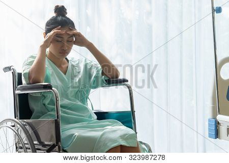 Serious Patient Sitting On Wheelchair In Hospital.