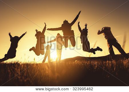 Big Group Of Happy Friends Jumps And Runs At Sunset Time. Travel Together Concept