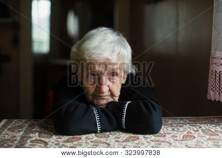 Portrait of a sad old woman. Care for lonely pensioners.