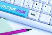 Handwriting text Welcome Home. Concept meaning Expression Greetings New Owners Domicile Doormat Entry White pc keyboard with empty note paper above white background key copy space. poster