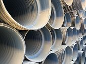 Stacked corrugated pvc-pipes at the outdoor warehouse. Drainage, plumbing, stormwater equipment poster