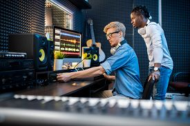 Young casual man adding volume while recording music with his African colleague in contemporary studio
