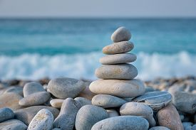 Zen meditation relaxation concept background - balanced stones stack close up on sea beach