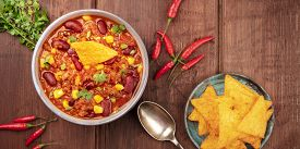 A Panorama Of Mexican Food. Chili Con Carne, Chilli Peppers, Cilantro Leaves, And Nachos, Shot From