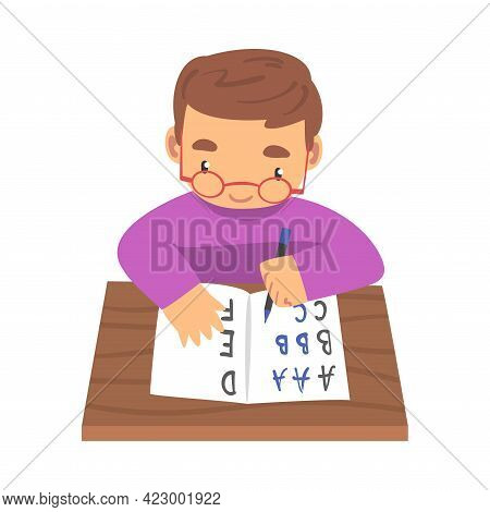 Little Boy Learning To Write, Elementary School Student Writing English Letters While Sitting At Des
