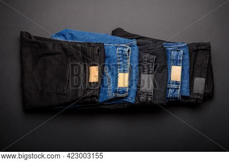 Denim Blue Jeans And Black Jean Stacked In Pile On Black Background Top View. Denim Jean Pants Wear