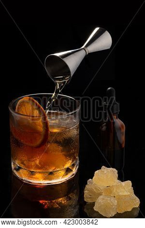 Alcoholic cocktail Old fashioned cocktail with orange slice, spilling bourbon from the double jigger, Glass Dropper Bottle with Pipette and lump sugar on black background. Copyspace