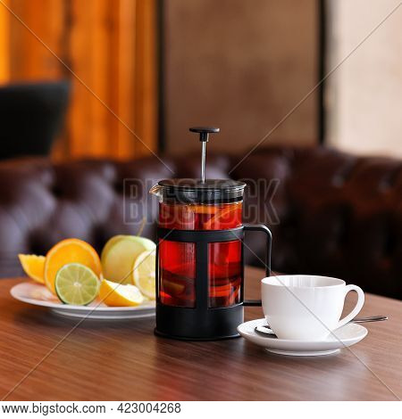 Brewed Black Tea. Full Teapot Or French Press Of Hot Drink On Wooden Table With Teacup And Plate Of