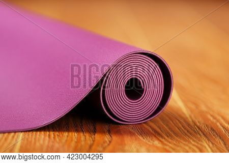 An Unfolded Lilac-colored Yoga Mat Is Unfolded On The Wooden Floor.